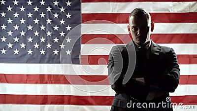Silhouette d'un homme d'affaires sérieux sur fond de drapeau américain clips vidéos