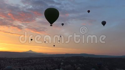Silhouette des ballons à air chauds volant au-dessus de Cappadocia au lever de soleil clips vidéos
