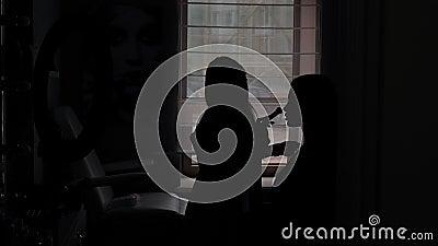 Silhouette di un artista di trucco da ragazza in un salone di bellezza mentre lavora con un cliente archivi video