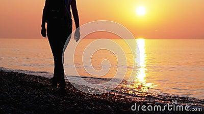 Silhouette einer Frau bei Sonnenuntergang entlang der Küste stock video