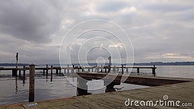 Silhouette einer Person, die in der Ferne paddelt, hinter einer Bootsanlegestelle am Washington-See stock video