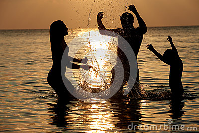 Silhouette Of Family Having Fun In Sea On Beach Holiday
