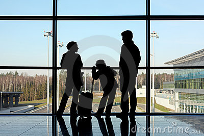 Silhouette of family with luggage near window