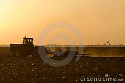 Silhouette of farmer tilling his land after the harvest.