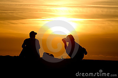 Silhouette of female photographer at sunset