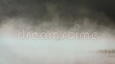 Silhouette of a fisherman on a boat in the morning mist on the lake. Silhouette of a fisherman on a boat in the morning dense fog on the lake. Early morning stock footage