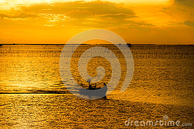 Silhouette of fishing boat and fishermen in sea