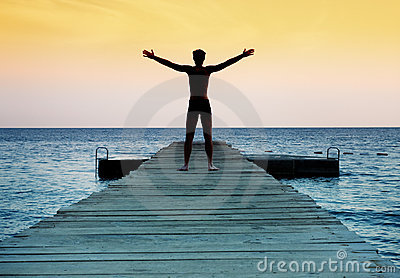 Silhouette of free peaceful man at sunset