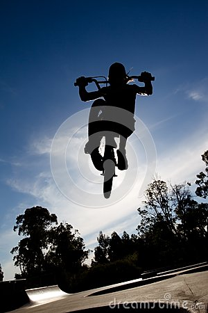 Silhouette of Freestyle BMX rider getting air
