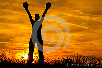 Silhouette of the girl with boxing gloves exercising