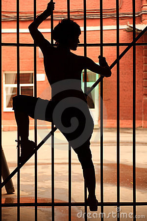 Silhouette of girl, she climbing on lattice