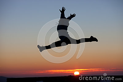 Silhouette of girl doing the splits jump in sunset