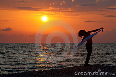 Silhouette of girl with handkerchief at sunset