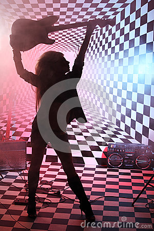 Silhouette of girl holding electric guitar overhead in studio