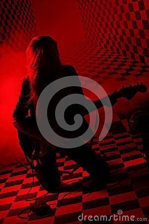 Silhouette of girl kneeling and playing electric guitar