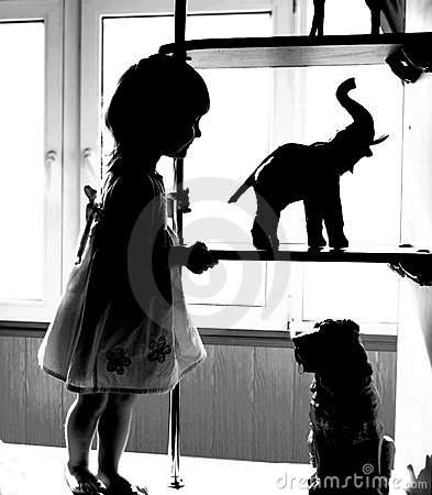 Silhouette of girl looking at animal toys
