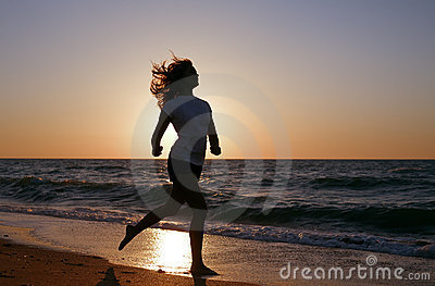 Silhouette girl run on sea coast