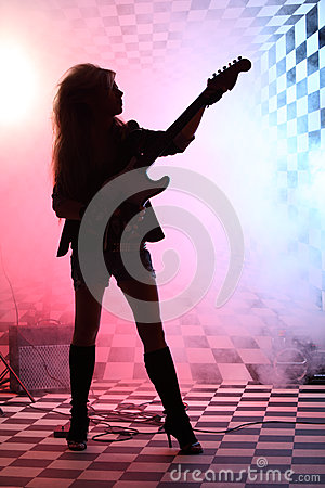 Silhouette of girl standing and playing electric guitar