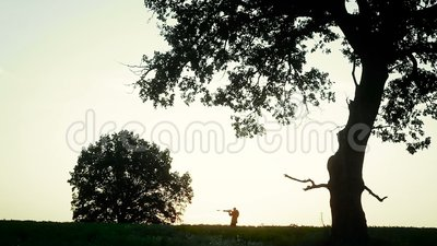 Hunter is on the field and aim. Silhouette of a hunter with a gun in his hands at sunset. A small figure of a hunter. He goes and aim at the prey. Around the stock video
