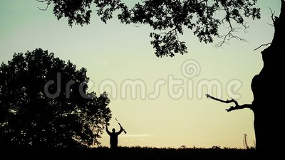 Hunter is on the field and aim. Silhouette of a hunter with a gun in his hands at sunset. A small figure of a hunter. He goes and aim at the prey. Around the stock footage