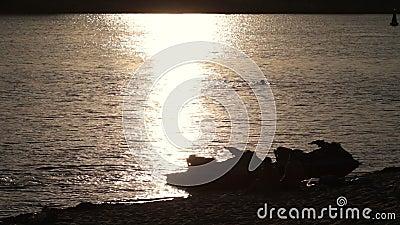 Silhouette jet ski on seashore in yellow sunset stock video footage