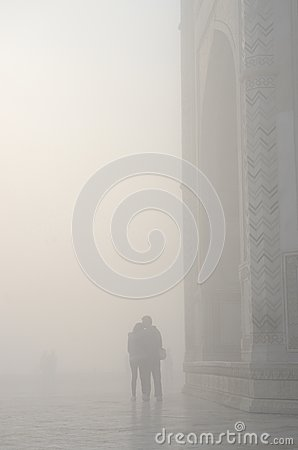 Silhouette of loving couple in a haze ,near Taj Mahal,India