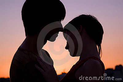 Silhouette of loving couple keeping hands together