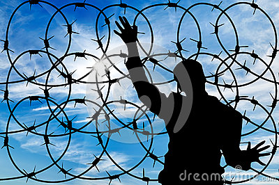 Silhouette male refugee and a barbed wire fence Stock Photo