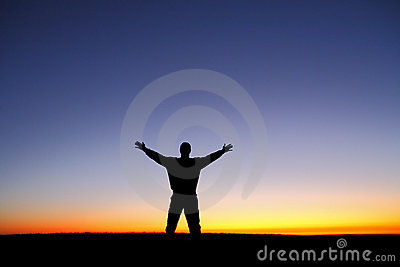 Silhouette of man with arms outstretched at sunset