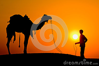 Silhouette of a man and camel at sunset in the desert, Jaisalmer - India