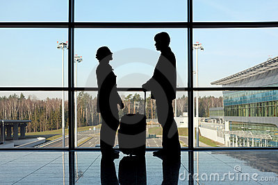 Silhouette of man and girl with luggage