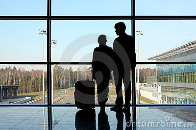 Silhouette of man and girl standing near window