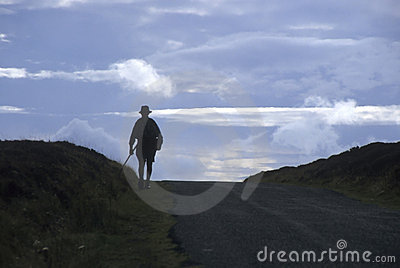 Silhouette of man hiking over hill