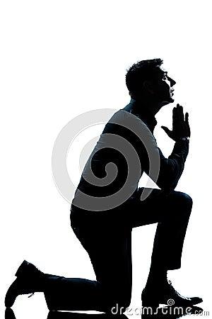 Silhouette man kneeling praying  full length