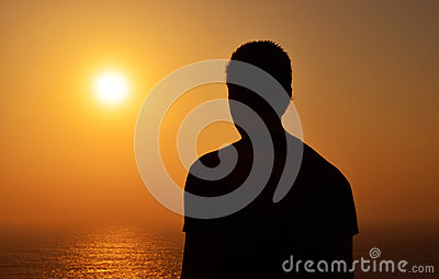 Silhouette of a man looking at algarve sunset