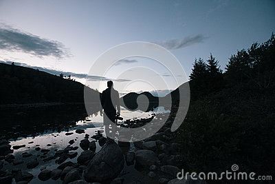 Silhouette Of Man Near Body Of Water Near Silhouette Of Trees And Mountains Free Public Domain Cc0 Image