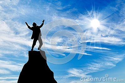 Silhouette of a man at the peak of the mountain Stock Photo