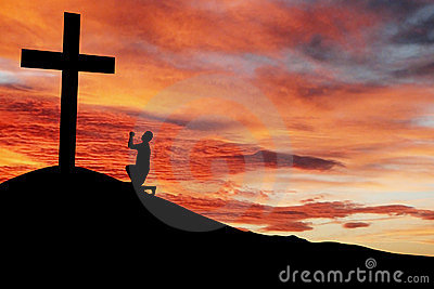 Silhouette of a man praying under the cross