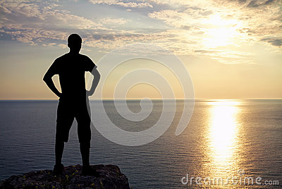 Silhouette of man on rock at sunset. Man on top of mountain.