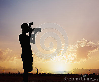 Silhouette of man taking photos with his camera at sunset with a dramatic sky