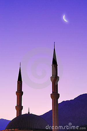 Silhouette of mosque and moon over sky