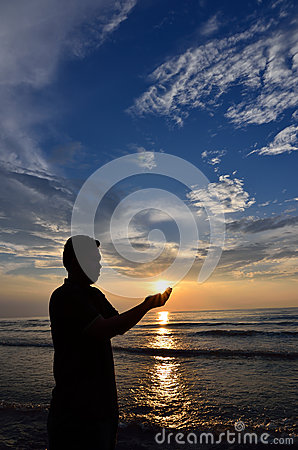 Silhouette of Muslim pray near the beach