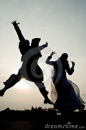 Silhouette of Newly Wedded Couple Jumping Happily