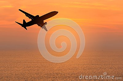Silhouette passenger airplane flying away in to sky high altitude during sunset time Stock Photo