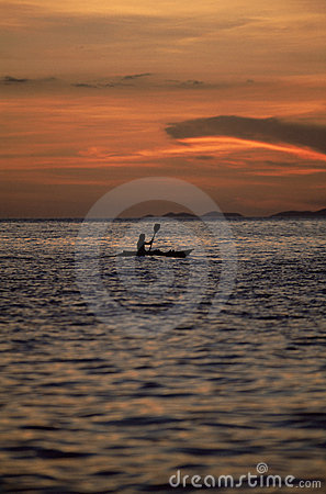 Silhouette of person kayaking at sea during sunset