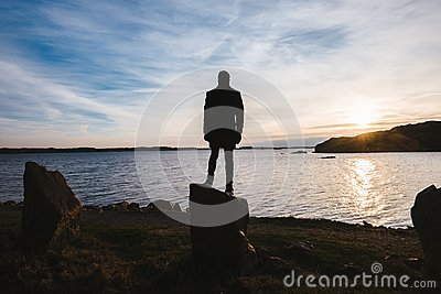 Silhouette Of Person Standing On Rock Near Body Of Water During Sunset Free Public Domain Cc0 Image