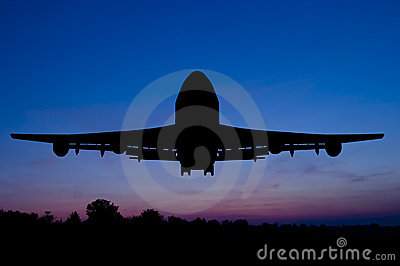 Silhouette of the plane on a sunset background.