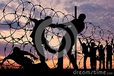 Silhouette of refugees and barbed wire Stock Photo