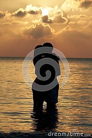Silhouette Of Romantic Couple Standing In Sea