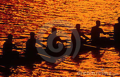 Silhouette of rowing crew at sunset